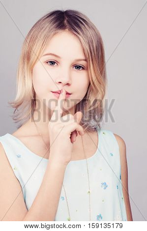 Young Girl with Blonde Bob Hairstyle. Teen Girl Holding her Finger to her Lips in a Gesture for a Secret. Female Teens Secrets