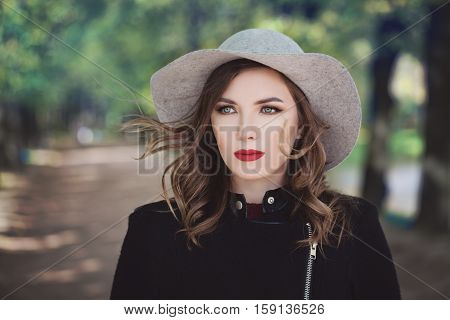 Beautiful Model Woman on Greenery Background Outdoors. Makeup Hairstyle a Grey Hat