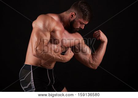 Close-up of a power fitness man's hand. Strong and handsome young bodybuilder demonstrate his muscles and biceps