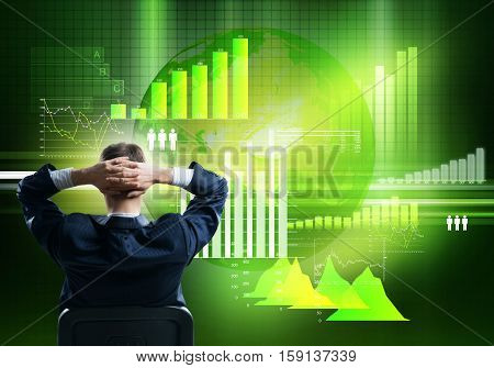 Back view of businessman sitting on chair with hands on head looking at virtual panel