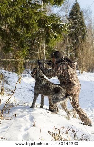 Hunter in camouflage aiming. with a dog. vertical shot