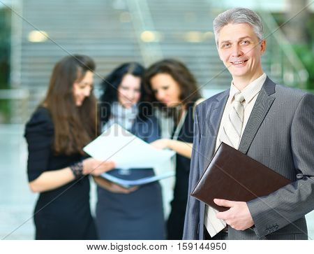 Manager of the company with documents on the background of the office