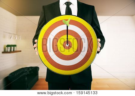 Man in suit holding dartboard with arrow in the middle. Modern room background. Aiming concept. 3D Rendering