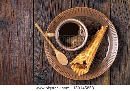 Cop of hot coffee and waffle cones with condensed milk in plate on old wooden table top view