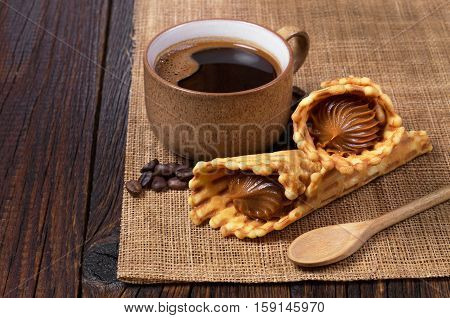 Cop of hot coffee and waffle cones with condensed milk on rustic wooden table