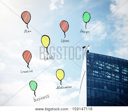 Young businessman on top of modern building on sky background with creative balloon sketches. Freedom concept