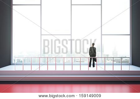 Businessman looking out of window in interior with red floor railing and city view. 3D Rendering