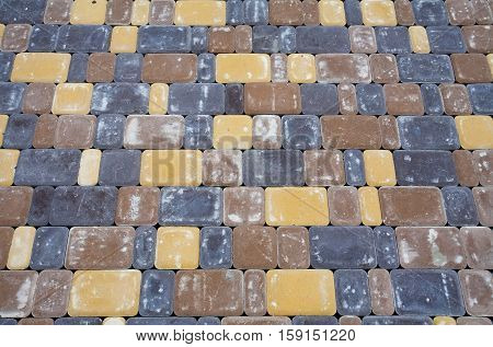 New paving tiles during installation. Traces of sand and cement.