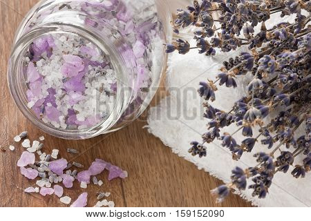 Aromatic sea salt lavender dried flower and soft towel on wooden background
