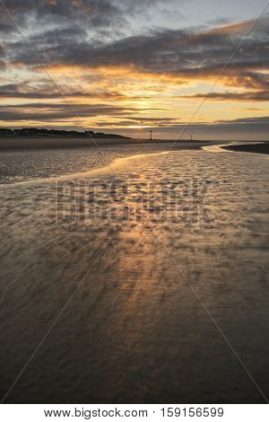 Beautiful Beach Coastal Low Tide Landscape Image At Sunrise With Colorful Vibrant Sky