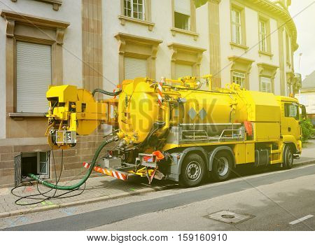 Working Sewage - sewerage - truck on city street in working process to clean up sewerage overflows cleaning pipelines and potential pollution issues from an modern building. This type of truck is used for residential septic systems or commercial sewage sy