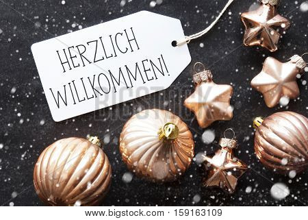 Label With German Text Herzlich Willkommen Means Welcome. Bronze Christmas Tree Balls On Black Paper Background With Snowflakes. Christmas Decoration Or Texture. Flat Lay View