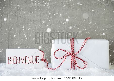 One Christmas Present On Snow. Cement Wall As Background With Snowflakes. Modern And Urban Style. Card For Birthday Or Seasons Greetings. Label With French Text Bienvenue Means Welcome