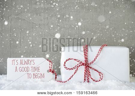One Christmas Gift On Snow. Cement Wall As Background With Snowflakes. Modern And Urban Style. Card For Birthday Or Seasons Greetings. Label With English Text Quote It Is Always A Good Time To Begin