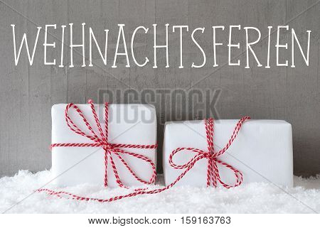 German Text Weihnachtsferien Means Christmas Holidays. Two White Christmas Gifts Or Presents On Snow. Cement Wall As Background. Modern And Urban Style.