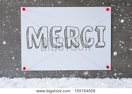 Label With French Text Merci Means Thank You. Urban And Modern Cement Wall As Background On Snow With Snowflakes.