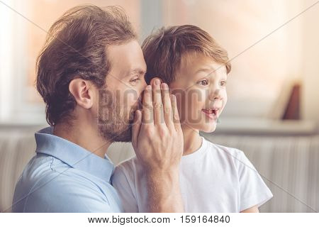 Father and son are smiling while spending time together at home