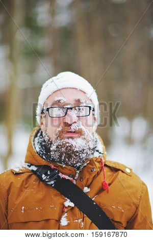 A young bearded man with glasses covered in snow while traveling through the taiga in winter.