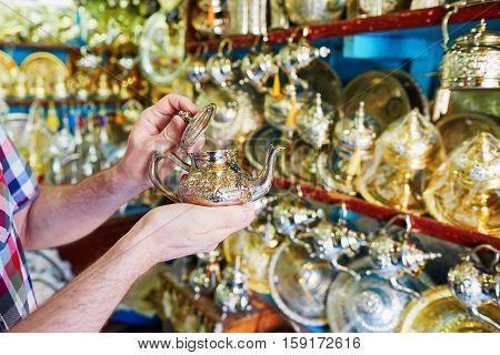 European Tourist Selecting A Teapot On Moroccan Market