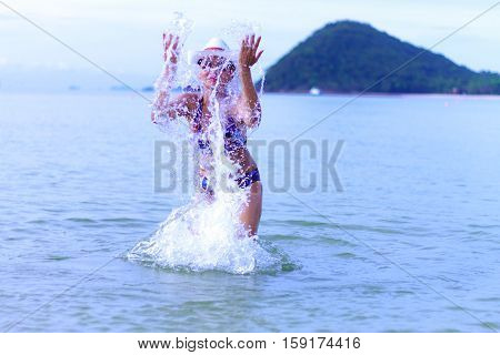 Women with bikini happy play water and hat on Thung Wua Lan Beach at Chumphon Province Thailand