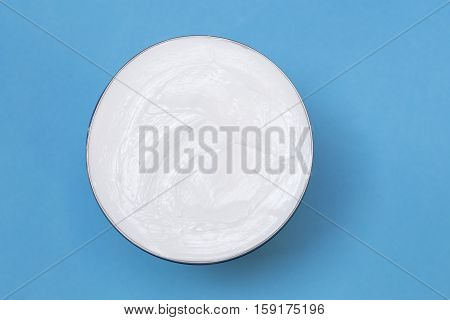 White face cream on a blue background