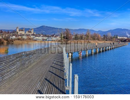 Rapperswil, Switzerland - 30 November, 2016: wooden pedestrian bridge over Lake Zurich between the town of Rapperswil and the village of Hurden - the longest wooden bridge in Switzerland.