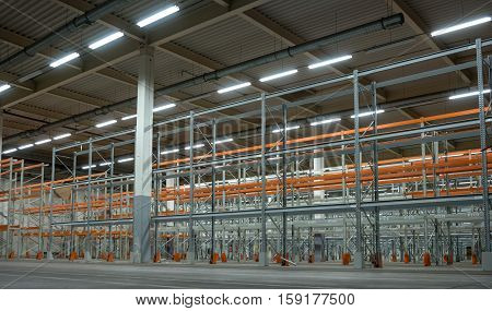 Interior of a warehouse with racks. Warehouse is not new - in the supporting pillars damaged paint.