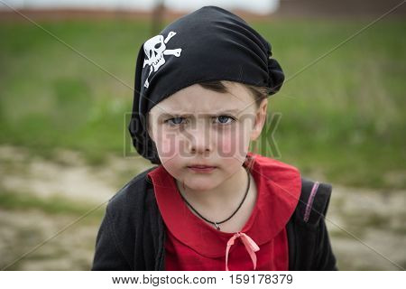 beautiful amazing funny little girl pirate in black bandana with skull and bones, ready for party