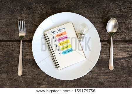 smart goals setting and hand written acronyms definition on the notebook and light bulb in a plate with spoon and fork on grunge table Business success concept