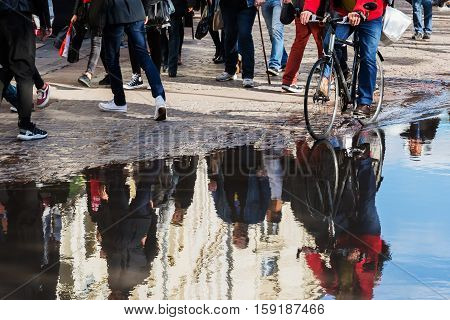 Walking People In The City Reflecting In A Puddle