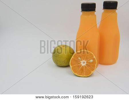 Fresh orange  fruit and  juice in a bottle on white background.