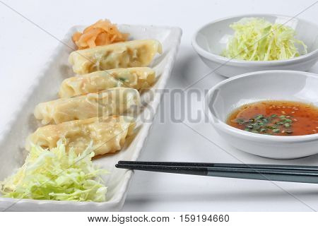 Close up of Japanese steamed stuffing flour with pork and cabbage as Gyoza with side disk. Selective focus.