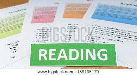 green card of english word and colorful reading english sheets on table