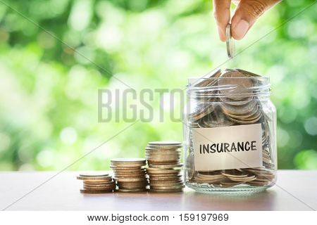Hand putting Coins in glass jar for money saving insurance concept