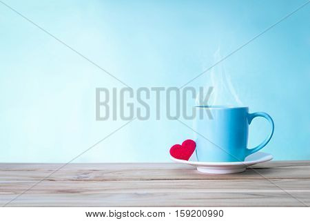 Coffee cup mug with red heart shape on wooden table Romance and love valentines day background concept