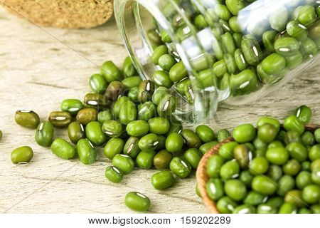 close up the green mung beans in wooden spoon on wood plate