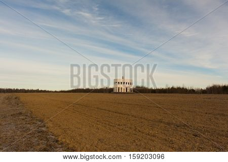 Small wooden house in the field. winter landscape.