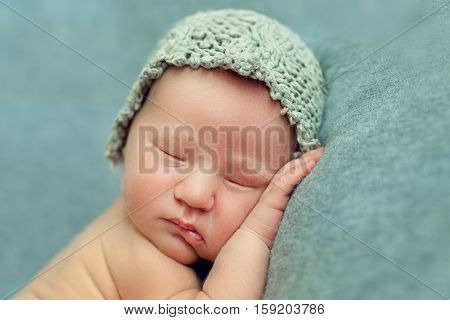 Newborn baby boy sleeping in the fetal position on a blue background in a knitted cap Face closeup