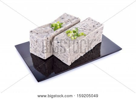 tofu mix black sesame seeds on black plate with white background