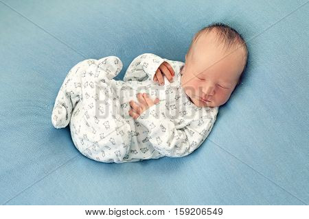 Newborn boy asleep on a blue background in white pajamas with a print. Morning sweet dream baby