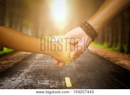 Mother holding a hand of her son walking on the street