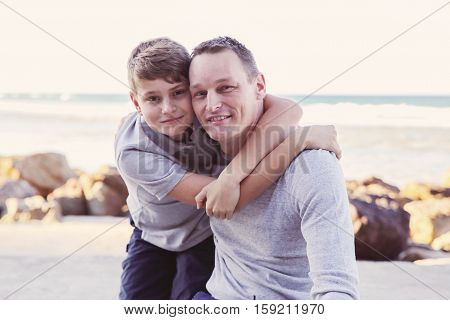 Father and son hugging on the beach toning