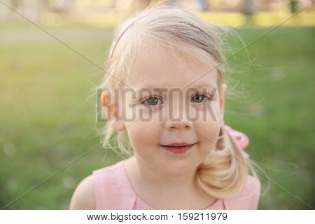 Cute little girl in pink dress in the park