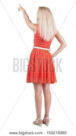Back view of young blonde woman pointing at wall. beautiful girl in dress. Rear view people collection. backside view of person. Isolated over white background.