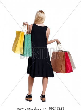 back view of woman with shopping bags . beautiful brunette girl in motion.  backside view of person.  Isolated over white background. Long-haired blonde in a black dress holding colored bags.
