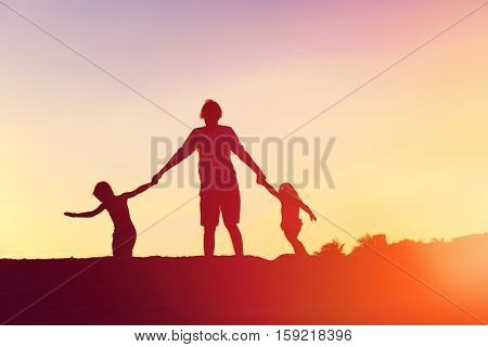 father with little son and daughter silhouettes play at sunset