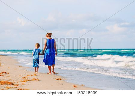 mother and little son walking on tropical beach, family beach vacation