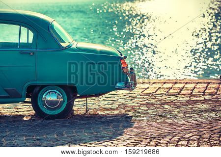 Vintage car near the sea and sparkling water as a background