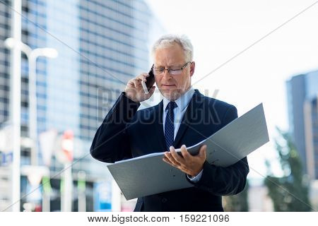 business, technology, communication and people concept - senior businessman with document folder calling on smartphone in city
