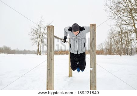 fitness, sport, exercising, training and people concept - young man doing triceps dip on parallel bars outdoors in winter